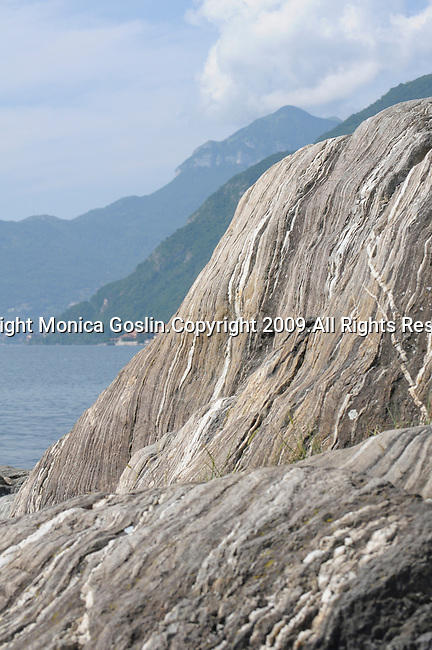 The rocky land in Rezzonico against the mountains of Lake Como, Italy makes an abstract landscape.