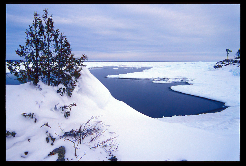 TREES CLING TO CLIFFS OVER LAKE SUPERIOR IN THE SNOW ON THE KEWEENAW PENINSULA NEAR COPPER HARBOR MICHIGAN.
