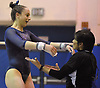 Miranda Lund of Plainview JFK, left, gets congratulated by coach Debbie Rut after her performance on the uneven bars which earned her a score of 9.35 in the Nassau County varsity gymnastics individual championships and state qualifier at Long Beach High School on Tuesday, Feb. 13, 2018.