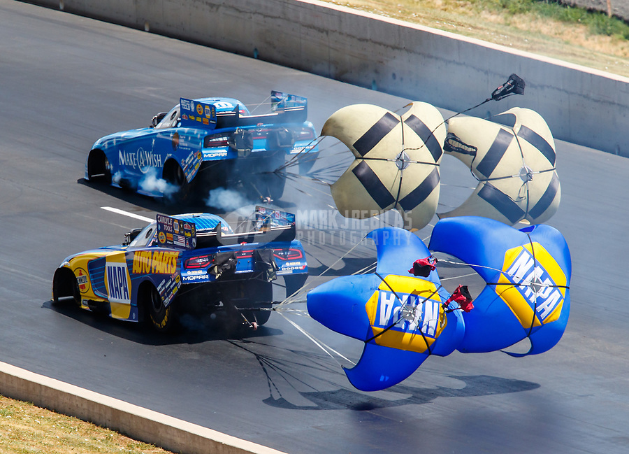 Jul 23, 2017; Morrison, CO, USA; NHRA funny car driver Ron Capps (near) deploys his parachutes alongside Tommy Johnson Jr during the Mile High Nationals at Bandimere Speedway. Mandatory Credit: Mark J. Rebilas-USA TODAY Sports