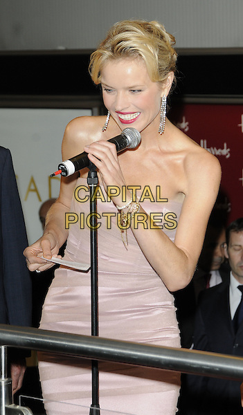 EVA HERZIGOVA .At the opening of the Harrods Summer Sale, Harrods, Knightsbridge, London, England, UK, June 19th 2010..half length dangly earrings hair up strapless beige nude microphone smiling red lipstick dress hand speaking pink pale .CAP/CAN.©Can Nguyen/Capital Pictures.