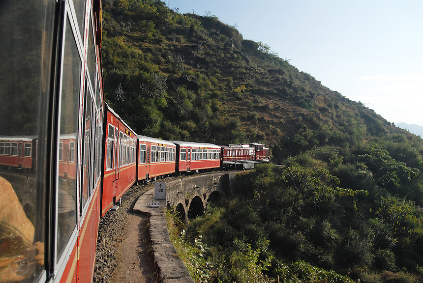 "The ""Himalayan Queen"" train, which connects Kalka with Shimla (Simla),  rounds a bend in the forested mountains."