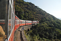 """The """"Himalayan Queen"""" train, which connects Kalka with Shimla (Simla),  rounds a bend in the forested mountains."""
