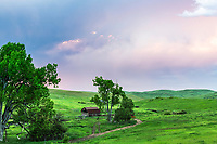 Prairie Sunset, Red Lodge Montana.  A setting sun lights up the stormy sky and the emerald green prairie of spring.  An old log barn adds an ambiance of the frontiersmen who settled her a century and a half ago.