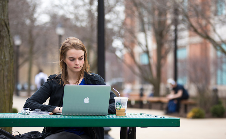 Student Katy Bozich takes advantage of the spring weather and works outside on DePaul's Lincoln Park Campus. DePaul University / Jeff Carrion)