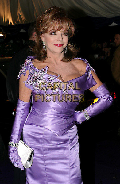 JOAN COLLINS .British Comedy Awards at London Television Studios .10 December 2003.half length, half-length, long purple dress, gown, long gloves, flower accessory, clutch bag, handbag.www.capitalpictures.com.sales@capitalpictures.com.© Capital Pictures.