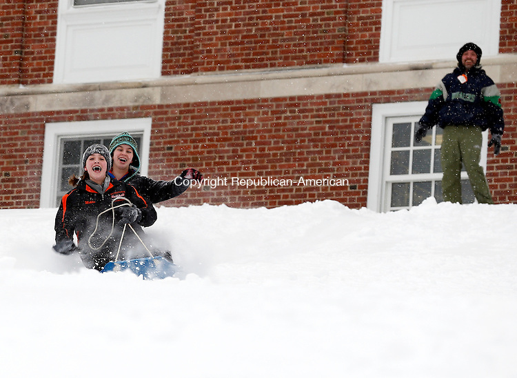Middlebury, CT- 02 February 2015-020215CM05-  Hannah Mehlin, 14, front, and friend Emily Gurksy, 14, of Watertown  have a laugh as they sled down Shepardson Hill in Middlebury on Monday.  Looking on is Mehlin's father, Kirk Mehlin.  Christopher Massa Republican-American