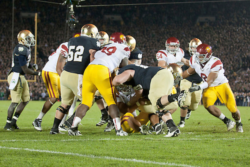 Players of Notre Dame and USC battle on the goal line during third quarter of NCAA football game between Notre Dame and USC.  The USC Trojans defeated the Notre Dame Fighting Irish 31-17 in game at Notre Dame Stadium in South Bend, Indiana.