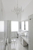 The all-white bathroom features a double wash basin and a cool marble floor