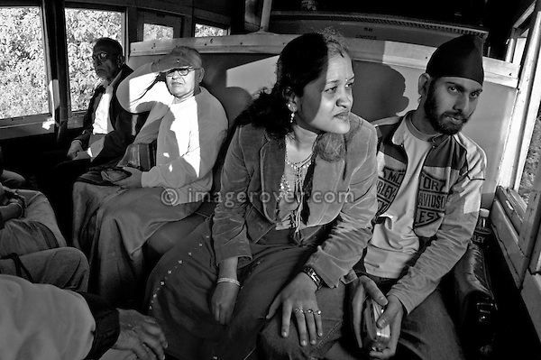 Indian passengers in the Nilgiri Mountain Railway (steam train) descending through the Nilgiri Mountains from Coonoor to Mettupalayam. India, Tamil Nadu 2005. --- Info: The Nilgiri Mountain Railway (NMR) is the only rack railway in India and connects the town of Mettupalayam with the hill station of Udagamandalam (Ooty), in the Nilgiri Hills of southern India. The construction of the 46km long meter-gauge singletrack railway in Tamil Nadu State was first proposed in 1854, but due to the difficulty of the mountainous location, the work only started in 1891 and was completed in 1908. This railway, scaling an elevation of 326m to 2,203m and still in use today, represented the latest technology of the time. In July 2005, UNESCO added the NMR as an extension to the World Heritage Site of Darjeeling Himalayan Railway.