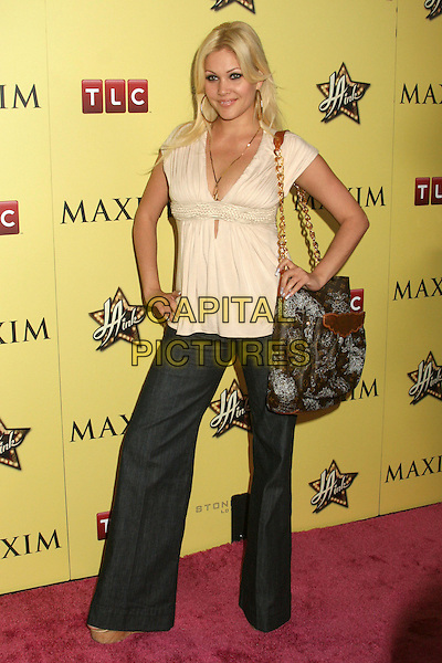 SHANNA MOAKLER.LA INK Premiere Party at the Sofitel Hotel's Stone Rose Lounge, Los Angeles, California, USA..August 6th, 2007.full length cream beige top brown bag purse wide leg jeans denim hands on hips.CAP/ADM/BP.©Byron Purvis/AdMedia/Capital Pictures
