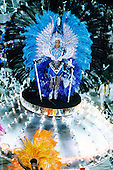 Rio de Janeiro, Brazil. Carnival dancer in blue and gold sequinned costume with large gold headdress.