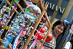 A woman looks at Edo furin, or glass wind chimes, displayed on a wooden frame by seller Yoshitomo Sasaki in the chic Ginza district in Tokyo, Japan. The chimes, which date back more than 200 years in Japan, were traditionally carried around town dangling from  bamboo poles by sellers. Sasaki is one of a few people who continue this trend.