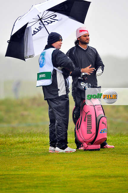 Johan Edfors shelters from the wet conditions on the 9th hole during Round 2 of the 3 Irish Open on 15th May 2009 (Photo by Eoin Clarke/GOLFFILE)