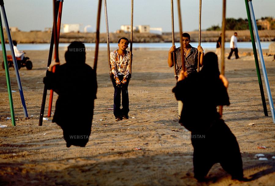 2002. Saudi Arabia. Young Saudi men and women flirt from a distance, seated on swings on one of Jeddah's beaches during the festivities of the Eid-ul-Fitr. The women wear the abaya, a long black tunic covering the body from head to toe. Arabie Saoudite. Jeu de séduction à distance entre des jeunes hommes et des jeunes femmes, assis sur l'une des plages de Djedda, pendant les festivités de l'Eid-ul-Fitr. Les femmes portent l'abaya, une longue tunique noire qui couvre le corps de la tête aux pieds.