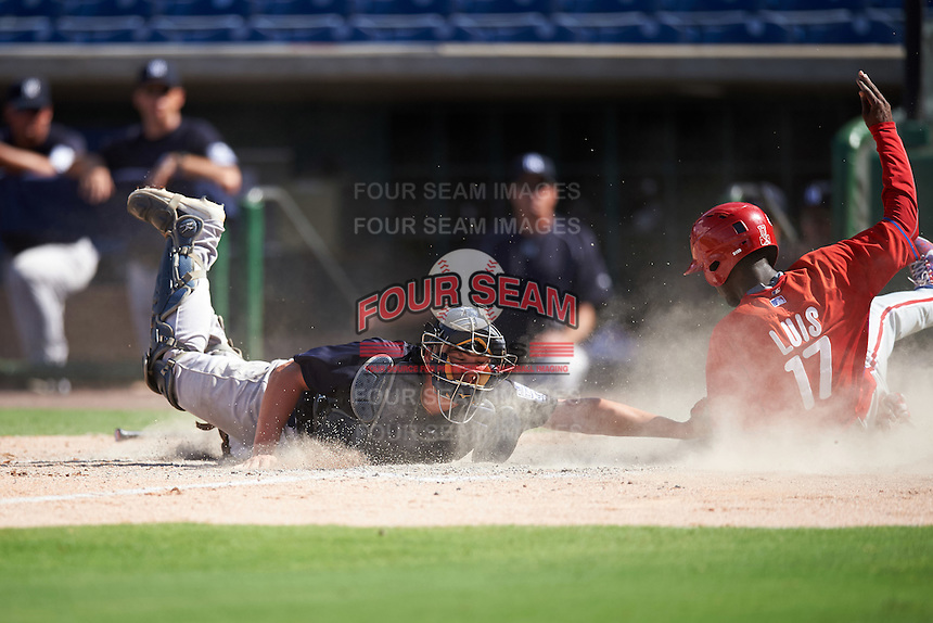 New York Yankees catcher Donny Sands (57) lunges to tag Juan Luis (17) sliding into home during an Instructional League game against the Philadelphia Phillies on September 27, 2016 at Bright House Field in Clearwater, Florida.  (Mike Janes/Four Seam Images)