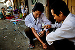 Two men wearing business shirts openly shoot up in an alleyway slum, where children play. Phnom Penh's slums are also home to Vietnamese drug users because the drug laws are more strict in Cambodia's neighboring country.