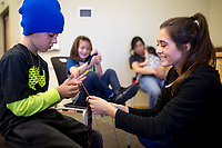 """NWA Democrat-Gazette/CHARLIE KAIJO Alyssa Hobbs (from right) helps Riley Shelby, 9, of Bentonville make a scarf by way of finger knitting during the """"How-To"""" festival, Saturday, March 24, 2018 at the Bentonville Library in Bentonville. <br /><br />Participants learned how to create a Duck Tape® corner bookmark, design a balloon rocket racer, discover finger knitting, write a Haiku poem, paint a watercolor masterpiece and learn about BookFlix®"""