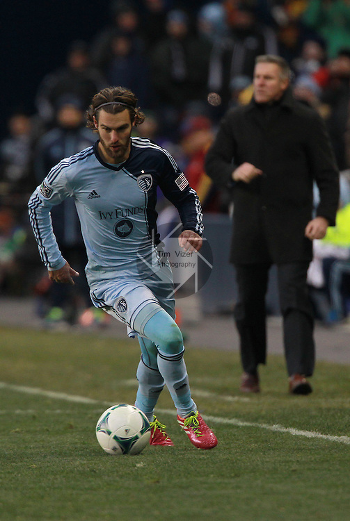 Sporting KC midfielder/forward Graham Zusi (8) dribbles the ball downfield.  In background is Sporting KC head coach Peter Vermes. Sporting KC defeated Real Salt Lake in a shootout after the score was tied 1-1 at the end of regulation play in the MLS Cup 2013 championship held at Sporting Park in Kansas City, Kansas on Saturday December 7, 2013.