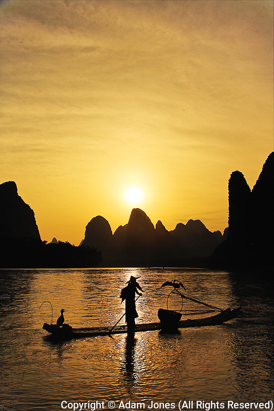 Traditional fisherman with cormorants and karst formations along Li River at sunset, near Guilin, China