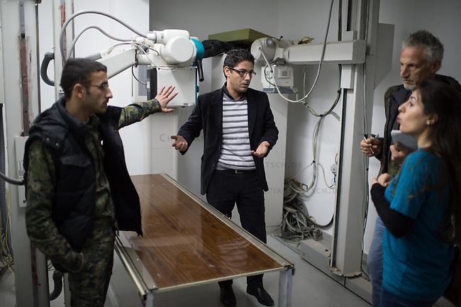 Sehid Xebat Hospital unter YPG-Verwaltung in Qamishli, Rojava/Syrien.<br /> Im Bild: Mitarbeiter des Krankenhauses erlaeutern einer Recherche-Gruppe der Medizinischen Hilfsorganisation PHNX aus Deutschland die technische Situation im Krankenhaus. Im Labor sind z.b: 98 Prozent alles Geraete defekt und auch im OP fehlt es an Ersatzteilen und Operationszubehoer und das Roentgengeraet im Bild ist defekt.<br /> 14.12.2014, Qamishli/Rojava/Syrien<br /> Copyright: Christian-Ditsch.de<br /> [Inhaltsveraendernde Manipulation des Fotos nur nach ausdruecklicher Genehmigung des Fotografen. Vereinbarungen ueber Abtretung von Persoenlichkeitsrechten/Model Release der abgebildeten Person/Personen liegen nicht vor. NO MODEL RELEASE! Nur fuer Redaktionelle Zwecke. Don't publish without copyright Christian-Ditsch.de, Veroeffentlichung nur mit Fotografennennung, sowie gegen Honorar, MwSt. und Beleg. Konto: I N G - D i B a, IBAN DE58500105175400192269, BIC INGDDEFFXXX, Kontakt: post@christian-ditsch.de<br /> Bei der Bearbeitung der Dateiinformationen darf die Urheberkennzeichnung in den EXIF- und  IPTC-Daten nicht entfernt werden, diese sind in digitalen Medien nach &sect;95c UrhG rechtlich geschuetzt. Der Urhebervermerk wird gemaess &sect;13 UrhG verlangt.]