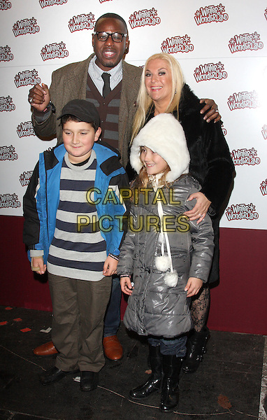 BEN OFOEDU, VANESSA FELTZ & guests .Winter Wonderland VIP Preview at Hyde Park, London , England, UK, .November 18th 2010..full length couple brown wool tweed green coat black fur lace tights patterned jeans ankle boots children kids .CAP/ROS.©Steve Ross/Capital Pictures