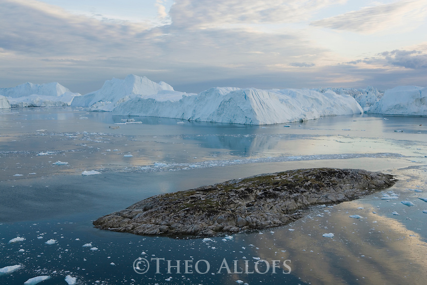 Rocky island and large icebergs at midnight, end of June, mid summer night; Disko Bay, Greenland