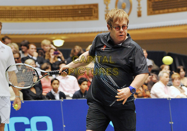 "Sir Elton John.The annual ""World TeamTennis Smash Hits"" charity night of tennis in Cleveland for the first time in the event's 19-year history, held at Public Hall, Cleveland, OH, USA..October 27th, 2011   .WTT half length athlete sport black top    ball racket racquet tinted  glasses    .CAP/ADM/JN.©Jason L Nelson/AdMedia/Capital Pictures."