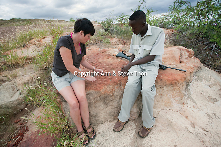 Ann playing ancient game of Moruba on Mapungubwe hill at Mapungubwe National Park with guide Moses Baloyi, Limpopo Province, South Africa