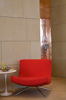 A retro style red chair is placed beside an Eero Saarinen table in the lobby of the Marques de Riscal wine complex and hotel