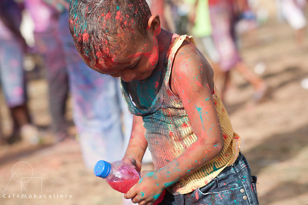 Young boy having fun squirting his bottle of pink dye