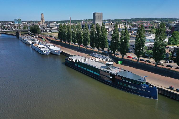 oto: VidiPhoto<br /> <br /> ARNHEM/DODEWAARD - Cruiseschepen en rondvaartboten liggen al anderhalve maand werkloos aan de Rijnkade in Arnhem (foto) en in de Waalhaven bij Dodewaard. Vanwege de coronamaatregelen mogen er voorlopig geen passagiers aan boord en varen de schepen niet. In Arnhem liggen vooral cruiseschepen van Nederlandse maatschappijen. Bij de gemeente Arnhem hebben zij inmiddels een verzoek ingediend om geen liggeld te hoeven betalen. De haven van Dodewaard is voorlopig de ankerplaats voor de vloot toeristenschepen die normaal op de Europese rivieren vaart. Een deel van de schepen is eigendom van Scylla AG, een rederij uit Zwitserland die op verschillende Europese rivieren vaart. De totaal 32 schepen van de vloot liggen allemaal stil in verschillende havens. De schepen zelf hebben net hun grote winter-onderhoudsbeurten gehad.
