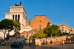 Busy street intersection with a view of the Altare della Patria on the left and the stairs leading up to the Basilica di Santa Maria in Ara coeli