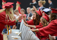 Ashley Beard, left, high fives Anna Robinson after receiving her diploma during the Plumstead Christian School's 36th Annual Commencement Saturday, June 11, 2016 at Plumstead Christian School in Plumstead, Pennsylvania. 39 seniors graduated from the school this year. (Photo by William Thomas Cain)