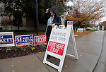 CORNELIUS, NC - NOVEMBER 1:  Facing a cold, wet day, Beverly Thomas, a poll worker at Cornelius Town Hall in Cornelius, N.C., sets-out a voting sign while waiting for the last day of early voting to open on Saturday, November 1, 2014.  North Carolina candidate for U.S. Senate Thom Tillis and Democratic incumbent Kay Hagan were both expected to campaign in Cornelius later in the day.  Tillis was expected to vote at the Cornelius Town Hall.  Thomas said she worried the weather would limit voter turnout.  (Photo by Ted Richardson/For The Washington Post)