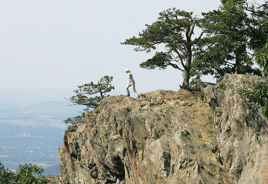 Jackie Speak of Suffolk, Virginia walks to the edge of the Ravens Roost overlook in Nelson County Thursday while visiting the Blue Ridge Parkway on the first day of summer. Photo/Andrew Shurtleff