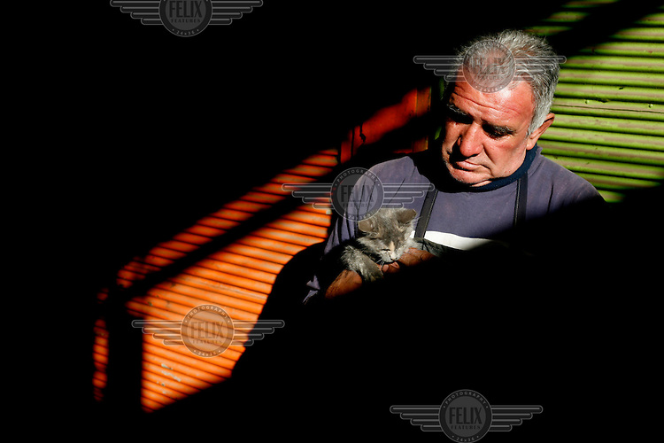 A man holds a kitten in the La Vega Central market.