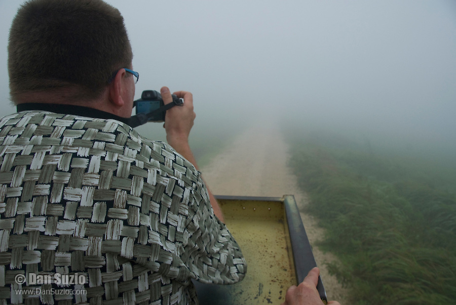 Herpetologist Hinrich Kaiser photographs the foggy landscape from the back of a truck on Atauro Island, Timor-Leste (East Timor)