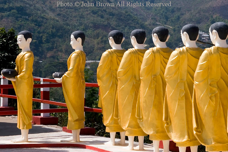 A row of tall gold Buddhist statues are on display at a beautiful