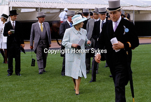Queen Elizabeth II & men with top hats walking on Epsom Race Course at The Derby. In foreground on right is Lord Porchester the Earl Carnarvon.