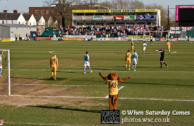 Newport County 1 Exeter City 1, 16/03/2014. Rodney Parade, League Two. Newport County finally return to the Football league after years of turmoil but a poor run of results has dented hopes of reaching the play-offs while Exeter City battle relegation. Match action with the away South End in the background. The Newport mascot 'Spytty' appeals for a decision from behind the goal. Photo by Simon Gill