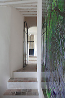 A glimpse down a corridor leading into the house past a wall featuring a photographic print entitled Dark Hedges and signed D.A. Hall