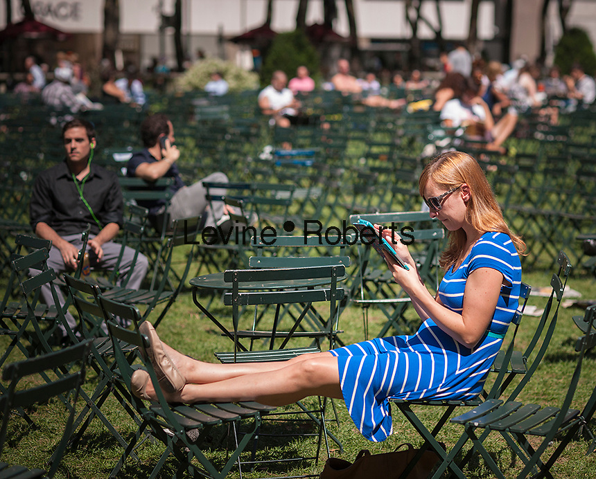 A visitor to Bryant Park in New York uses her tablet computer on Thursday, August 15, 2013.  (© Richard B. Levine)