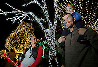 NWA Democrat-Gazette/DAVID GOTTSCHALK  Katy Fowler (left) looks on as her husband Kevin and son Dawson, 2, watch the Lighting Night parade of the Lights of the Ozarks on the downtown square in Fayetteville. The lights illuminate the square each evening from 5 p.m. to 1 a.m. through Dec. 31.