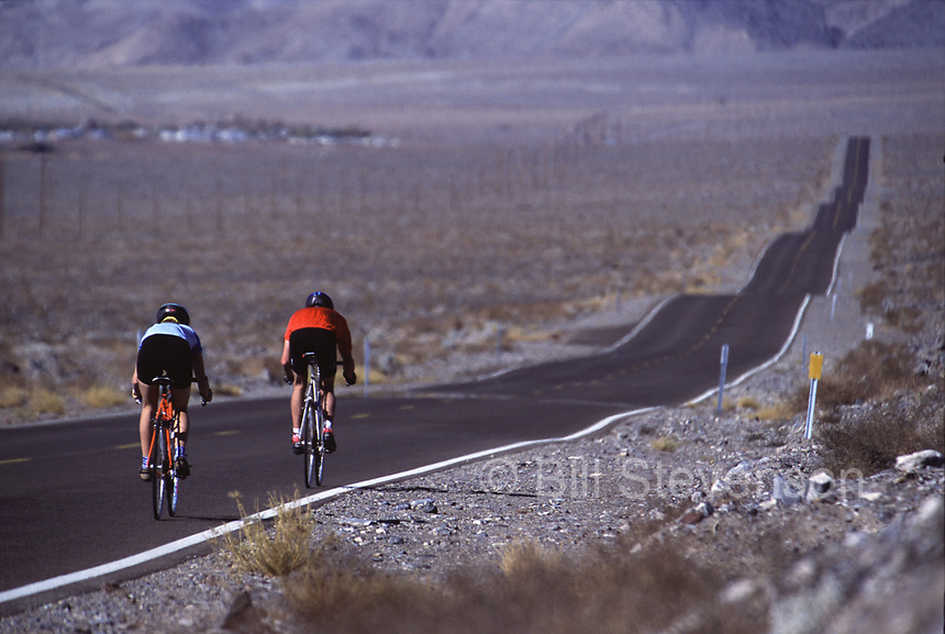 A picture of a man and a woman cycling down a long rolling highway in the desert of eastern California