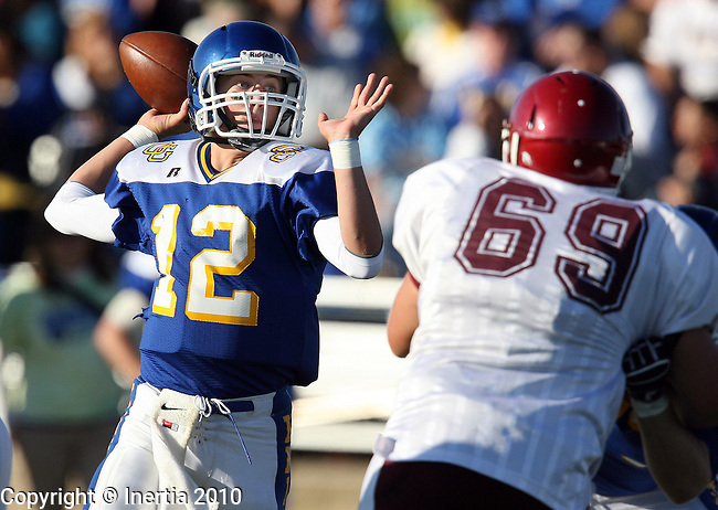 SIOUX FALLS, SD - SEPTEMBER 24:  Connor Schaefbauer #12 of O'Gorman looks for a receiver past the defense of Luke Gainey #69 from Spearfish in the first quarter of their game Friday evening at McEneaney Field. (Photo by Dave Eggen/Inertia)