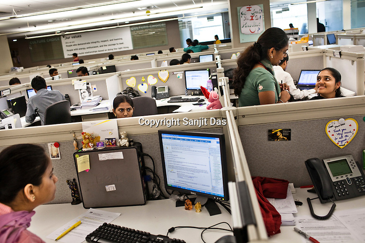 Ernst & Young employees are seen consulting while others work at the Ernst & Young Global Shared Services office in Bangalore, Karnataka, India. Ernst & Young has 49% women working for them in the India office. Photo: Sanjit Das