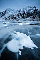 Rock breaks through ice on frozen lake Nedre Heimdalsvatnet, Eggum, Lofoten Islands, Norway