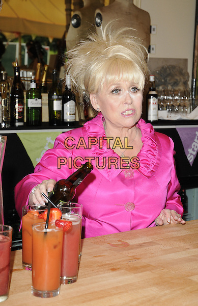 "BARBARA WINDSOR.""Launch of The Start Sustainable Pop-Up Restaurant with Think Eat Drink"",  .Lancaster House, Stable Yard, London, UK..July 26th, 2011.half length pink jacket bottle beer drink beverage cocktail juice pouring bar babs funny make-up eyes nose highlighter cover-up  powder.CAP/CAN.©Can Nguyen/Capital Pictures."