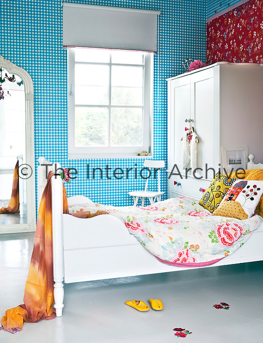 Zara's bedroom is a veritable extravaganza of bright colours and patterns, all unified by the white furniture and pale functional flooring